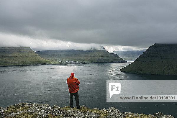 Wanderer betrachtet Aussicht  während er auf einer Klippe vor bewölktem Himmel steht