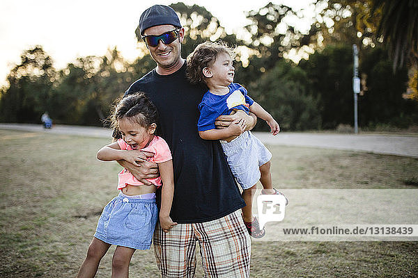 Portrait of playful father carrying daughters at park