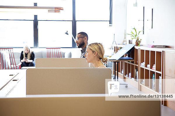 Seitenansicht von Geschäftsleuten,  die wegschauen,  während sie im Büro an Schreibtischen sitzen