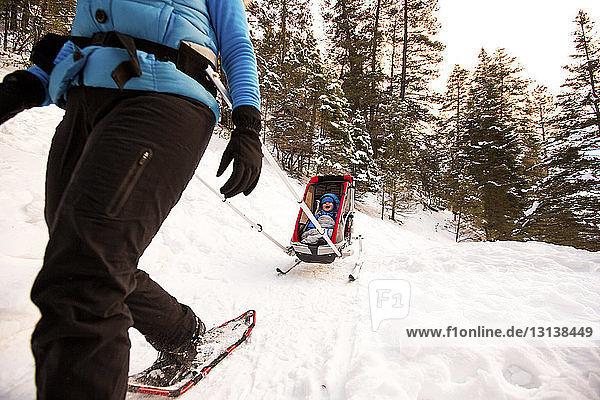 Niedrige Sektion einer Frau mit Sohn im Schlitten auf verschneitem Feld