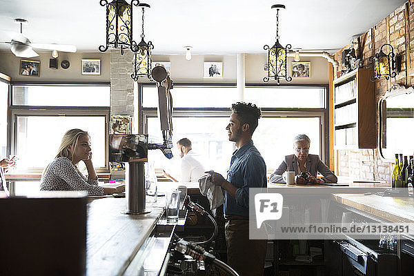 Smiling owner talking to customer while standing at bar counter in cafe