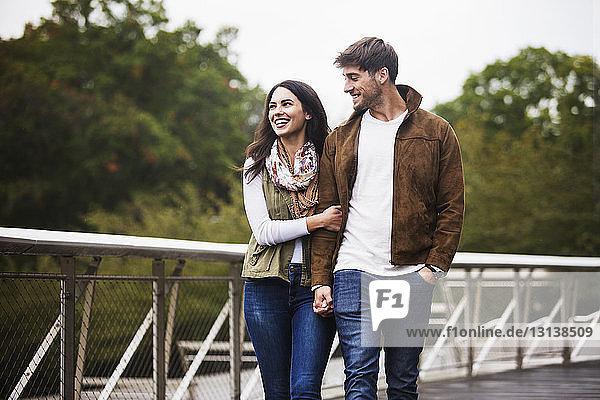 Glückliches Paar hält sich beim Gehen auf der Brücke bei klarem Himmel an den Händen