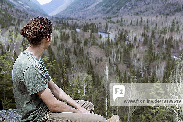 Thoughtful hiker sitting on mountain against trees