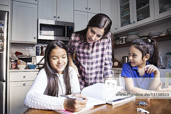 Mother looking girl studying in kitchen