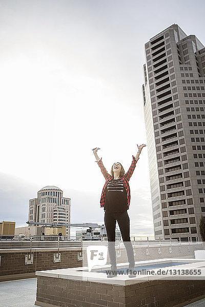 Glückliche Frau mit erhobenen Armen auf der Terrasse gegen den Himmel stehend