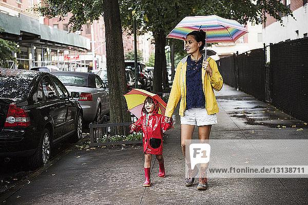 Glückliche Mutter und Tochter halten Regenschirme beim Gehen auf dem Bürgersteig