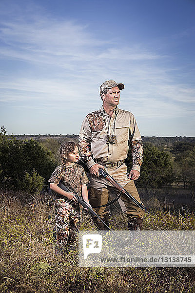 Thoughtful hunters with rifle standing on field against sky