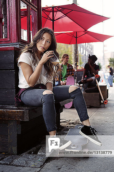 Nachdenkliche Frau trinkt Smoothie-Saft  während sie auf Stützmauer sitzt