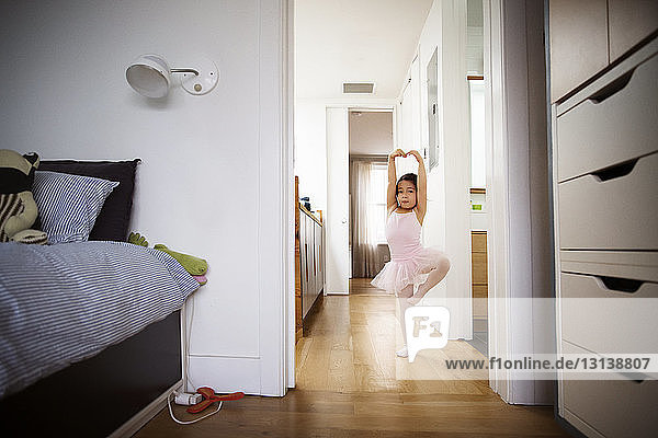 Girl practicing ballet on floor at home
