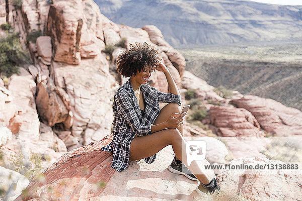 Frau benutzt Smartphone  während sie auf einer Felsformation sitzt