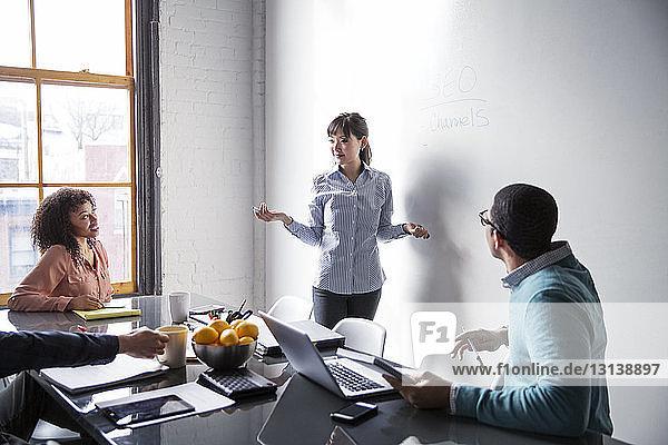 Geschäftsfrau erklärt Kollegen bei Treffen im Kreativbüro