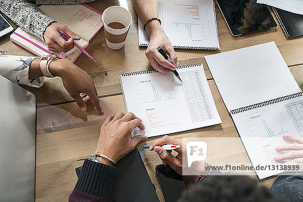 Cropped image of colleagues discussing graphs at table in office