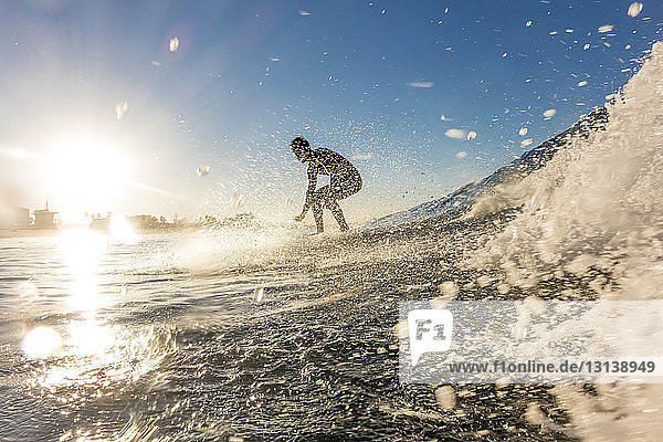 Man surfing on sea during sunset