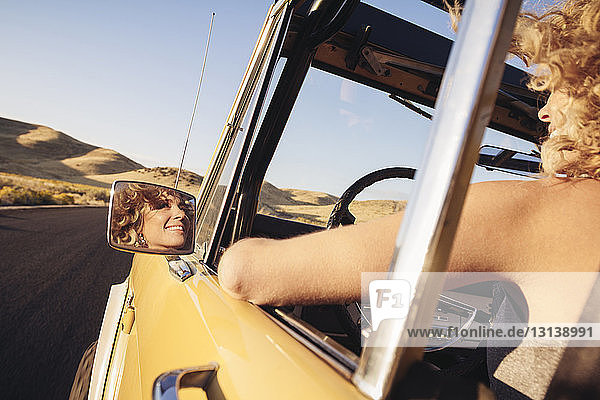 Cropped image of cheerful woman in off-road vehicle
