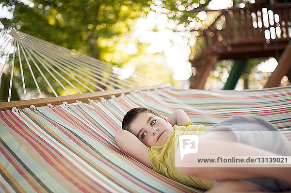 Thoughtful boy with hands behind head lying in hammock at park