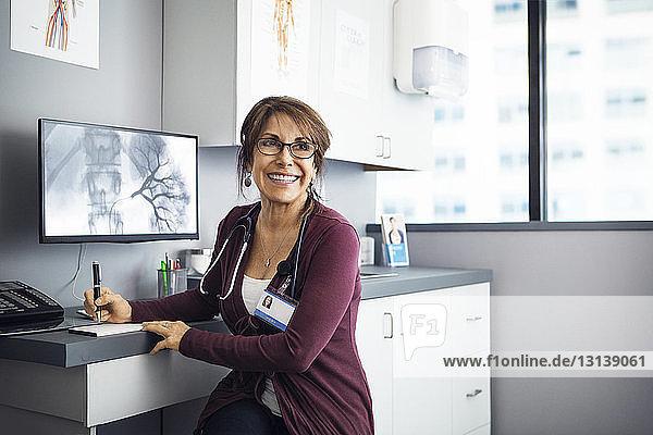 Glückliche Ärztin sitzt in der Klinik am Schreibtisch