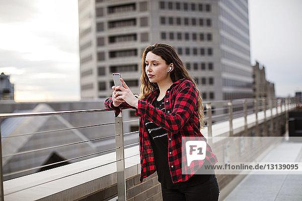 Junge Frau benutzt ein Smartphone  während sie auf der Terrasse am Geländer steht