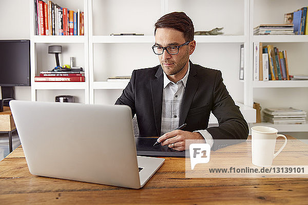 Businessman using graphics tablet and laptop computer at wooden table in home office