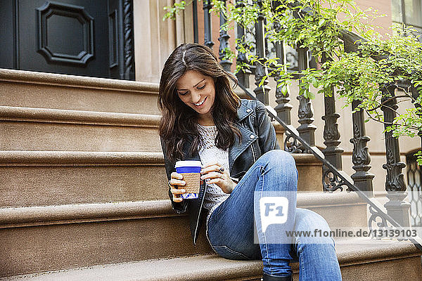 Glückliche Frau hält Einweg-Kaffeetasse in der Hand  während sie auf Stufen sitzt