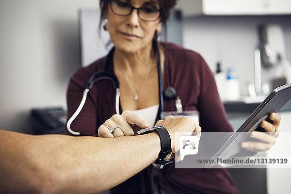 Ärztin prüft in der Klinik die Zeit auf der Armbanduhr der Patientin