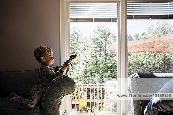 Junge spielt mit Spielzeug  während er zu Hause auf einem Sessel kniend sitzt