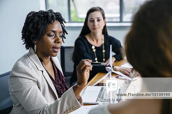 Geschäftsfrau erklärt Kolleginnen im Büro das Modell einer Windkraftanlage