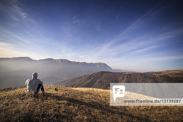 Rear view of man looking at view while sitting on Carpathian mountains