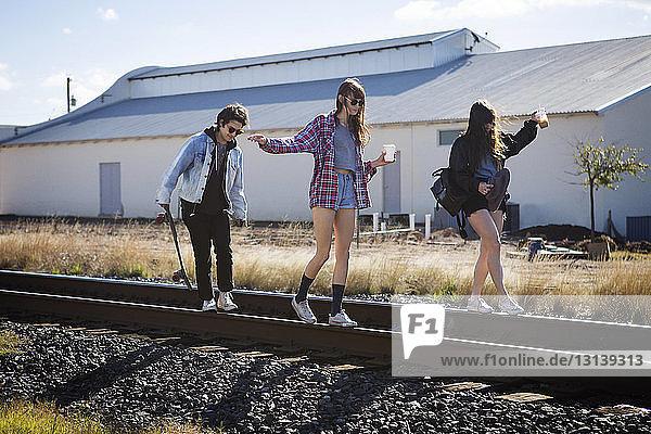 Spielerische Freunde gehen auf Eisenbahnschienen
