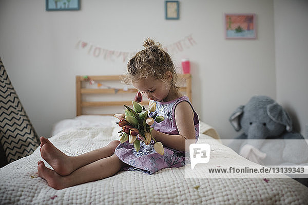 Girl holding tulips while sitting on bed at home