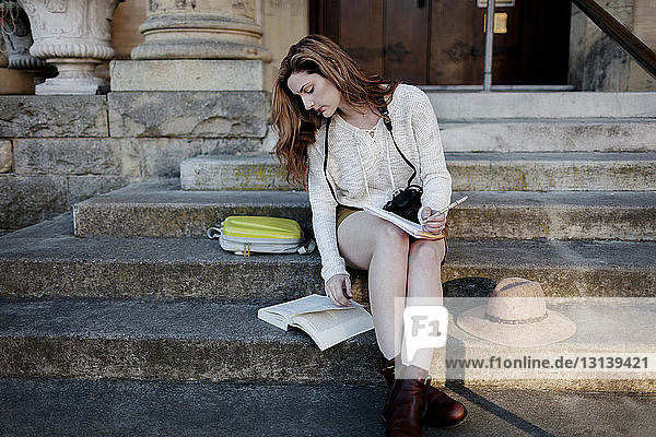 Full length of woman studying while sitting on steps