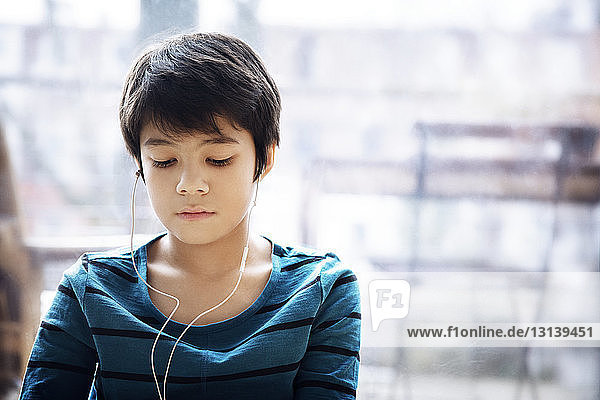 Close-up of boy with headphones looking down