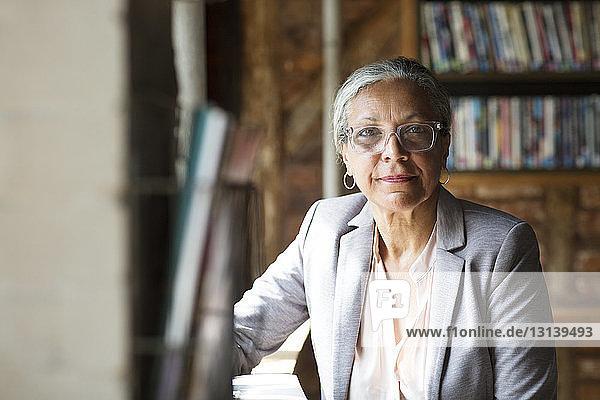 Porträt einer lächelnden Frau,  die in einem Cafe am Tisch sitzt