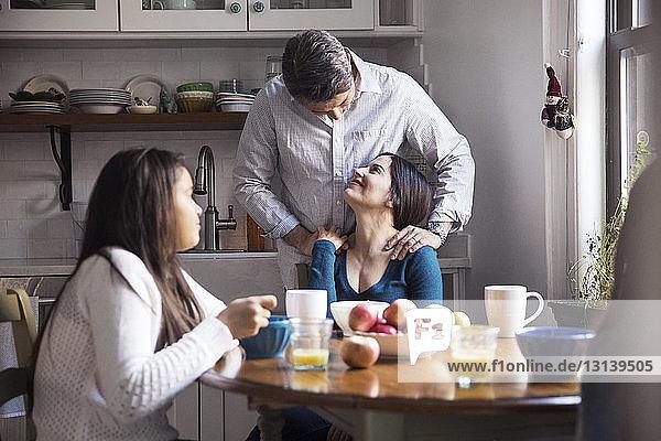 Glückliche Familie beim Frühstück am Tisch in der Küche