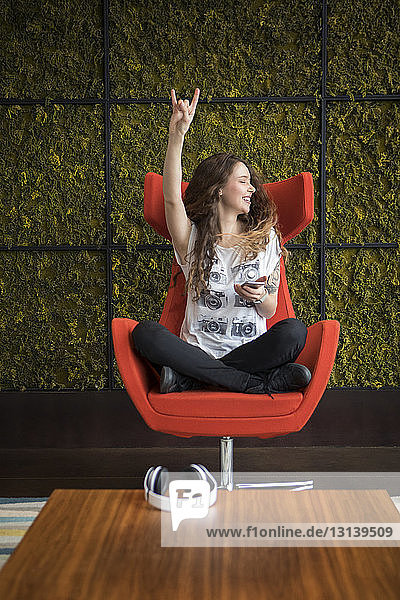 Glückliche Frau gestikuliert  während sie zu Hause auf einem Sessel sitzt