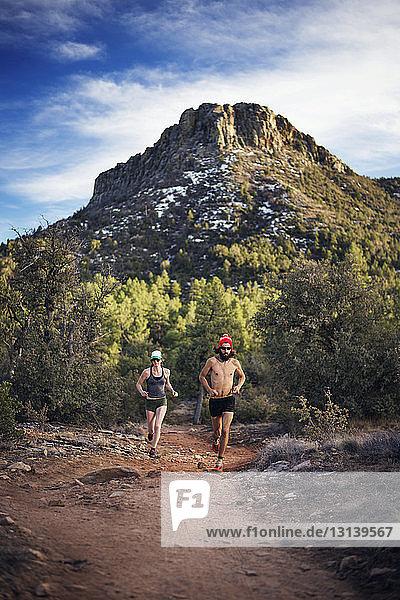 Entschlossenes Paar läuft auf Wanderweg durch Berg