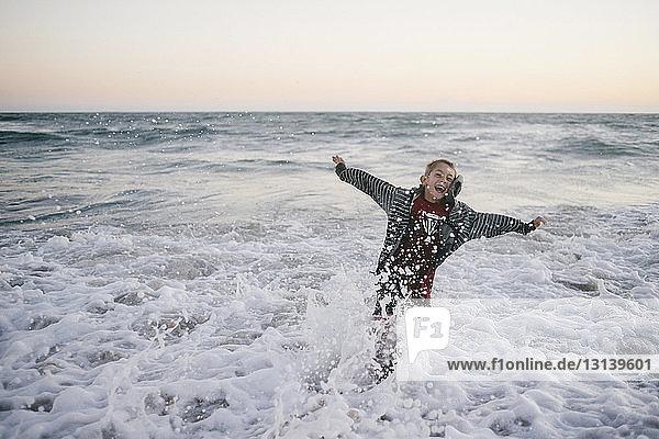 Cheerful boy enjoying on shore at beach against sky