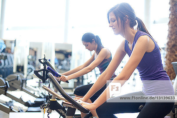 Side view of young women riding exercise bikes in gym