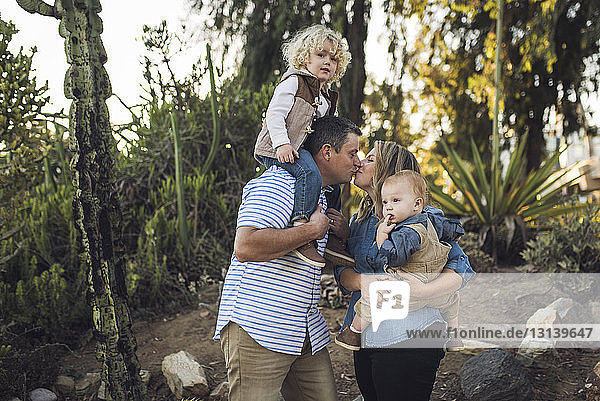 Parents carrying sons kissing while standing against plants at park