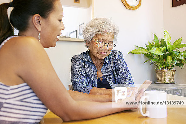 Daughter showing smart phone to senior mother on table at home