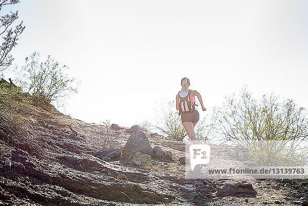 Rückansicht einer Wanderin mit Rucksack  die am sonnigen Tag auf dem Berg gegen den klaren Himmel läuft
