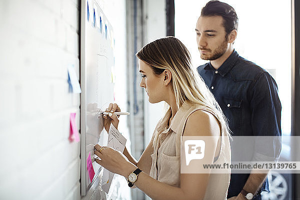 Geschäftsfrau schreibt am Whiteboard  während ein männlicher Kollege im Büro steht