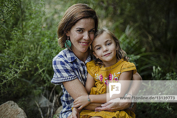 Portrait of mother and daughter against plants
