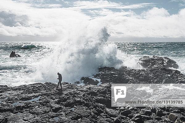 Full length of hiker against waves splashing on rocks at beach