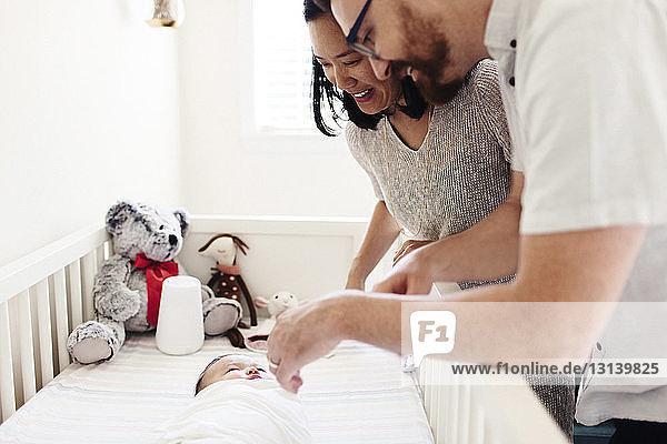 Glückliche Eltern schauen auf neugeborene Tochter  die zu Hause in der Krippe liegt