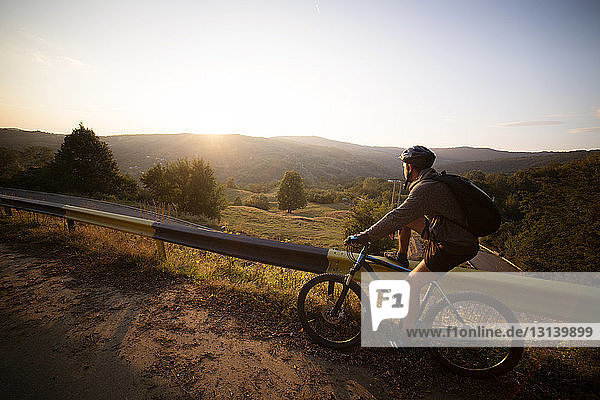 Side view of male athlete with bicycle by guard rail against clear sky