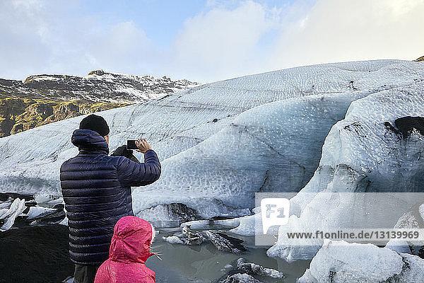 Rückansicht eines Vaters mit Tochter  der Gletscher fotografiert  während er gegen den Himmel steht