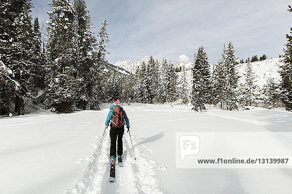 Rückansicht einer Frau mit Himmel  die auf einem schneebedeckten Feld gegen den Himmel im Wald läuft