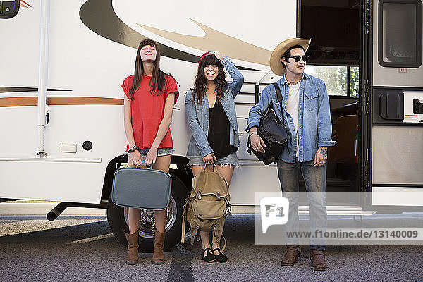 Friends carrying luggage while standing against camper van