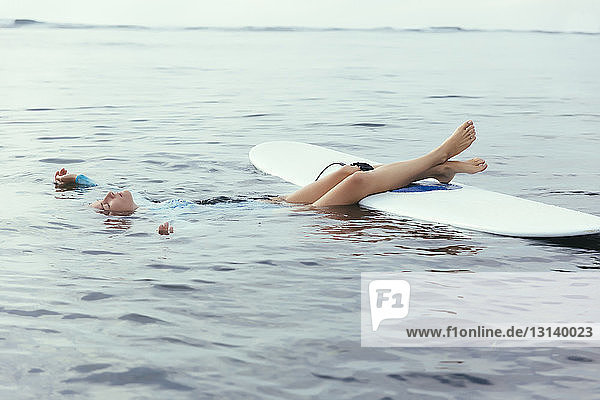 Woman with eyes closed floating while surfing on sea