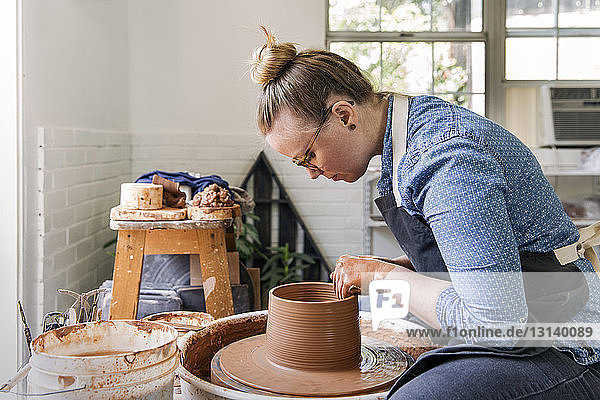 Side view of woman making pot at workshop